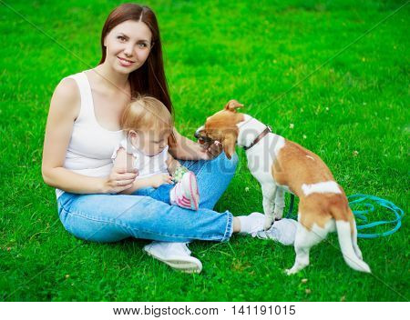 happy young mother with baby and her dog outdoors on a summer day