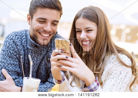 Young couple in love sitting in a cafe and communicating.Close up of a happy couple enjoying time together.They are wearing casual clothing.