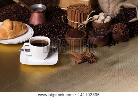 Still-life with coffee, cup with saucer, coffee mill, sac with beans and spices. Coffee time concept