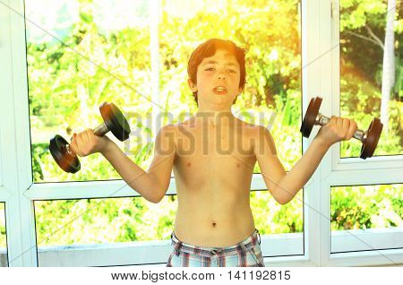 teenager handsome boy with dumb bells in gym exercise hands close up photo