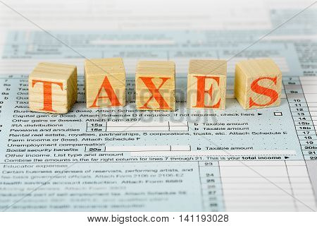 tax concept with wooden blocks on 1040 form