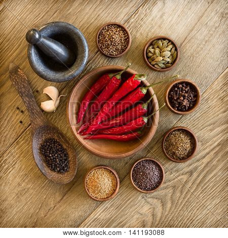 Spices in wooden bowls and mortar with pestle. Cooking ingridients, gourmet kitchen, eastern spices concept.
