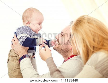 Parents spending quality time with their baby.A happy couple holding their beautiful baby and smiling.They are enjoying together and having a great time.