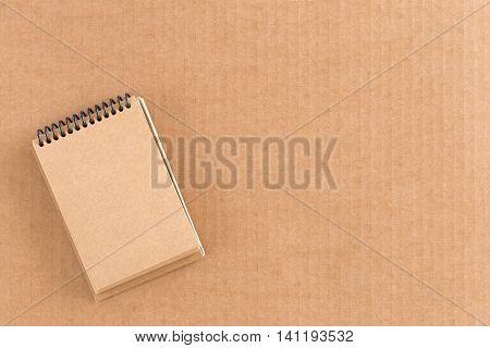 Brown cardboard notepad on corrugated cardboard background.