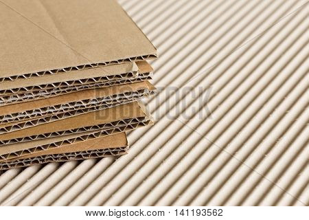 Cardboard pile on corrugated cardboard texture background.