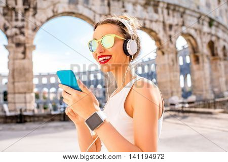 Young sports woman listening to the music with smarphone during the training near the ancient amphitheatre in Pula city.