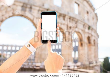 Female hands holding smartphone with white screen on the ancient amphitheatre background