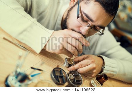 Close up portrait of a watchmaker at work.A watchmaker or repair man in actionviewing very closely.