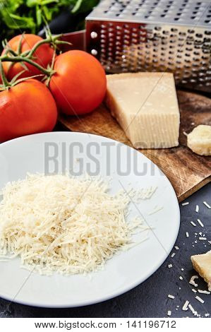 White plate with grated parmigiano reggiano or parmesan cheese on wood board on stone background. Tomatoes and grater on back. Parmesan uses in pasta dishes, soups, risottos and grated over salads.