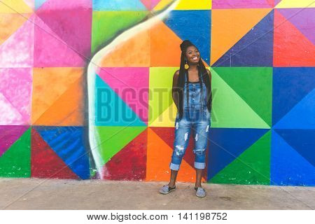 Young Afro woman smiling on colorful background