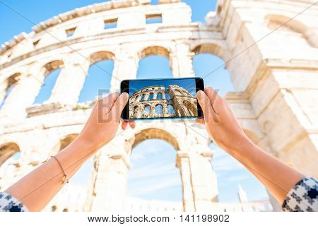 Female hands photographing with smartphone ancient amphotheatre in Pula, Croatia