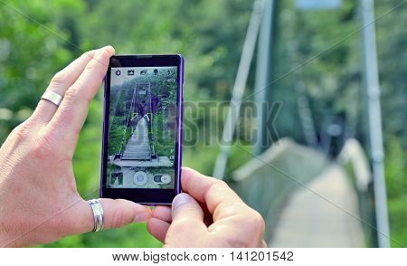 View over the mobile phone display during taking a picture of bridge in nature. Man is holding the mobile phone in hand and taking a photo in nature. Closeup view on hands with mobile phone.