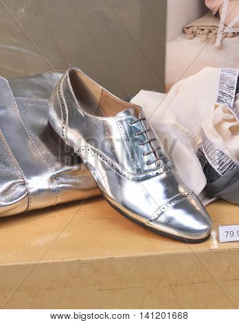 Shop window with silver shoe and scarf.
