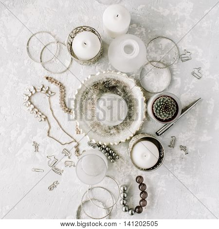 Flat lay top view concrete table desk. Decor collage with white feminine accessories candles silver decor clips and vintage golden tray on grey concrete background.