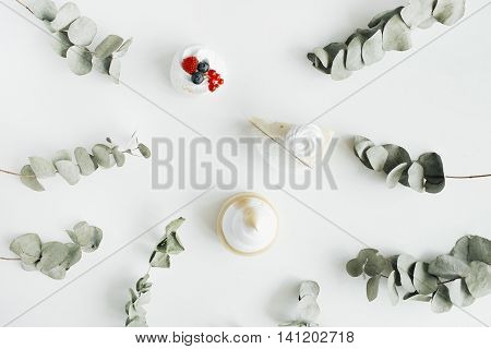 Breakfast composition with cakes and eucalyptus branches on with background. Flat lay top view