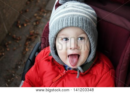 Cute naughty baby boy shows tongue and tease. Boy in winter knitting cap joke by opened mouth and tongue