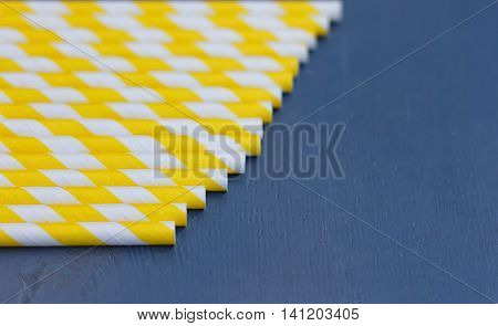 Striped straws for cocktails on blue wooden background