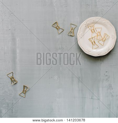 retro plate with golden clips on concrete background. flat lay top view