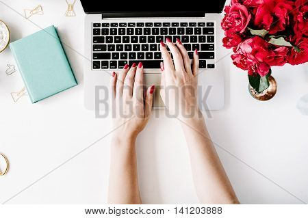 Flat lay top view office table desk. Workspace with girl's hands laptop red roses bouquet mint diary coffee mug and golden scissors on white background.