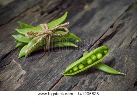 Fresh green peas on old wooden background
