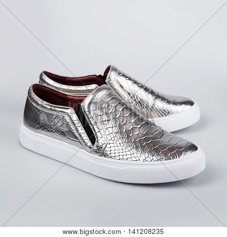 silver Italian shoes in a grey background