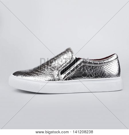 female silver shoes in a grey background