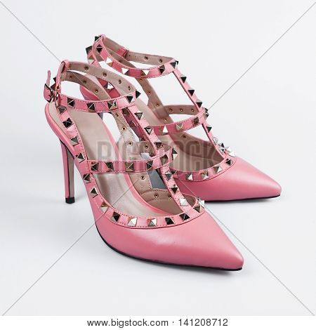 Female pink high heeled shoes over white