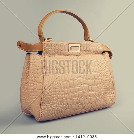 female beige handbag in a grey background