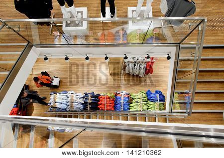 View from above over a clothes store with unrecognizable customers walking and buying modern clothes