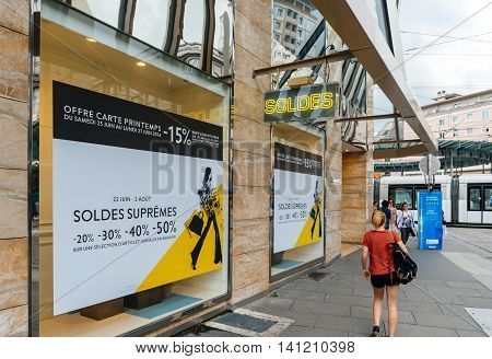 STRASBOURG FRANCE - JUNE 25 2016: Pedestrian walking near Printemps Luxuery store in Strasbourg with SOLDES Sales neon sign turned on and Sale advertising on windows