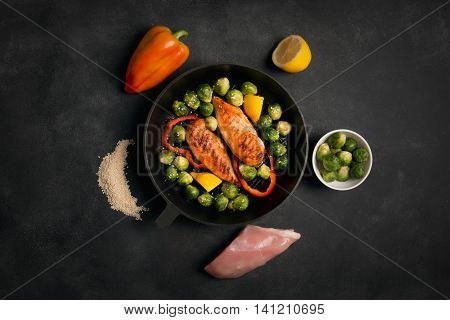 Chicken breasts cooked on the grill pan with Brussels sprouts and sesame on the black chalkboard