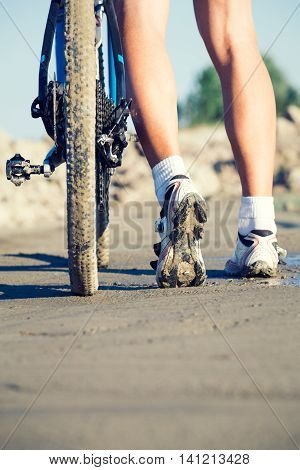 Cyclist's feet and a bike tire on the road