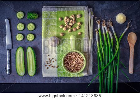 Green vegetables with seasoning on the dark stone background top view