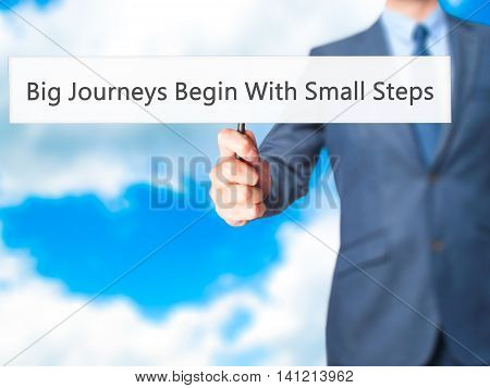 Big Journeys Begin With Small Steps - Businessman Hand Holding Sign