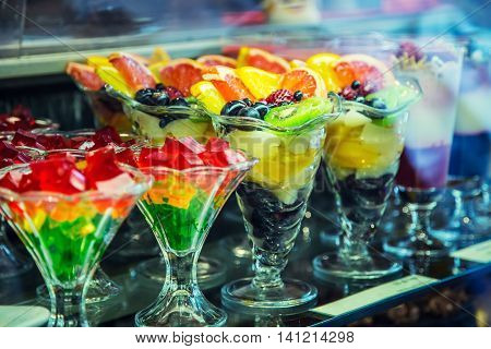 Colloured fresh summer fruits and gelatin sweet cups in confectionery shop.
