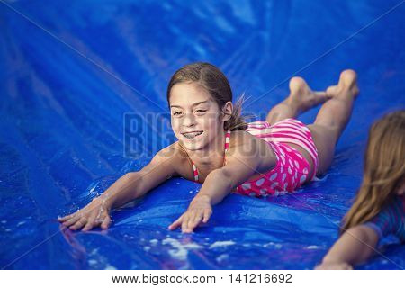 Smiling girl sliding down an outdoor slip and slide