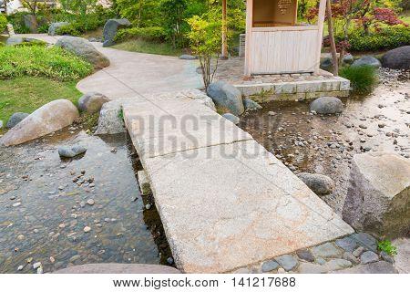 Stone Path In A Japanese Garden, Stone Bridge, Across A Pond.