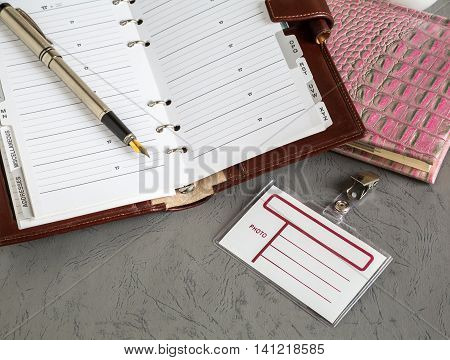 business objects a pen a notebook open on the table badge