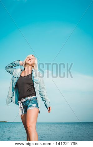 Tanned woman posing at the beach on summer day and and looking up. Dreamy female in jeans clothes standing on rocky coast blue sky background with sea. Concept holiday outdoors. Travel active lifestyle.