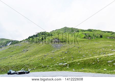 Photo of green capra peak two cars on a road and a field full of sheeps grazing in fagaras mountains Romania.