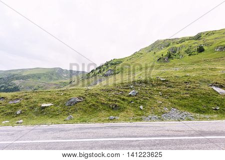 Photo of green capra peak a road in fagaras mountains Romania.