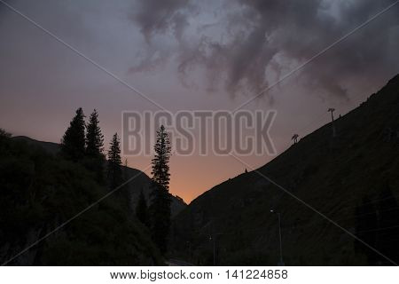 pine trees and mountains dark silhouette on cloud evening dusk sky backgroung sunset time