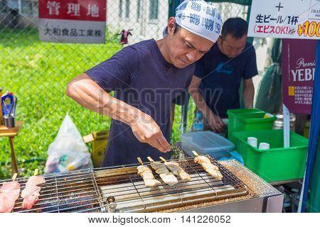 TOKYO JAPAN - 18 JULY 2016 - Street vendor man cooks fish on sticks at Tsukiji Fish Market in Tokyo Japan on July 18 2016