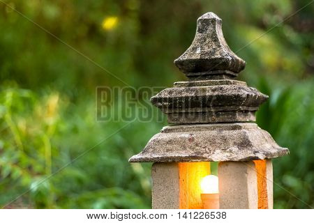 stone lantern lamp with light bulb inside in the green garden forest environment