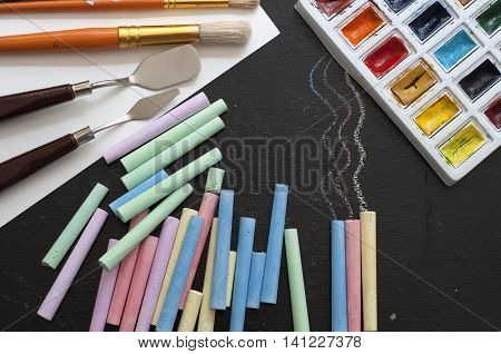 The art collection of assorted watercolor paint, brushes, palette knife, colored chalk on black background