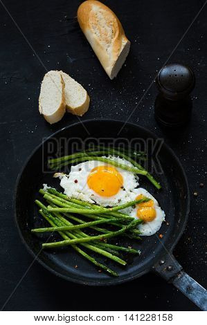 Fried eggs with asparagus in iron cast skillet, close up