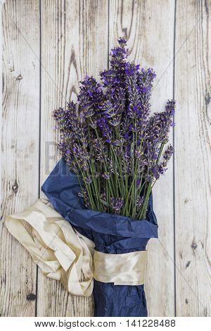 Bouquet of purple fresh fragrant lavender wrapped in blue paper with silk white ribbon on wooden background