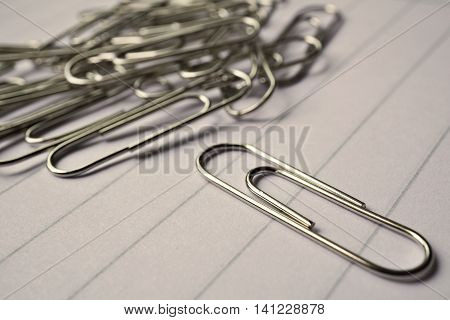 Heap of metal paper clips on white lined paper notepad as a symbol of typical office environment