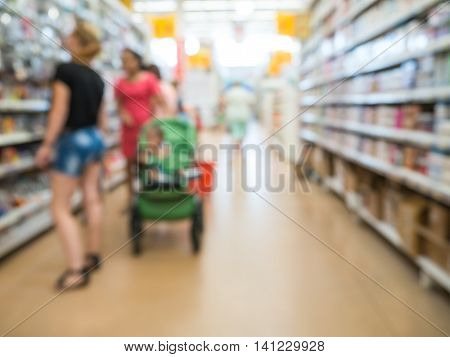 Abstract blurred supermarket aisle with unrecognizable customers as background