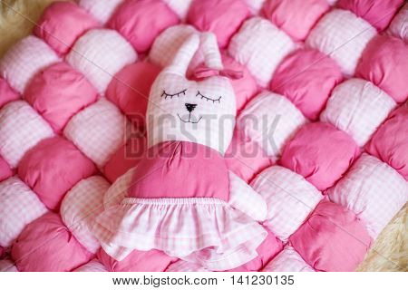 Cute little doll on pink checkered blanket. Pregnancy concept